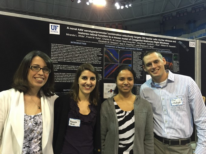 Four lab members standing in front of poster