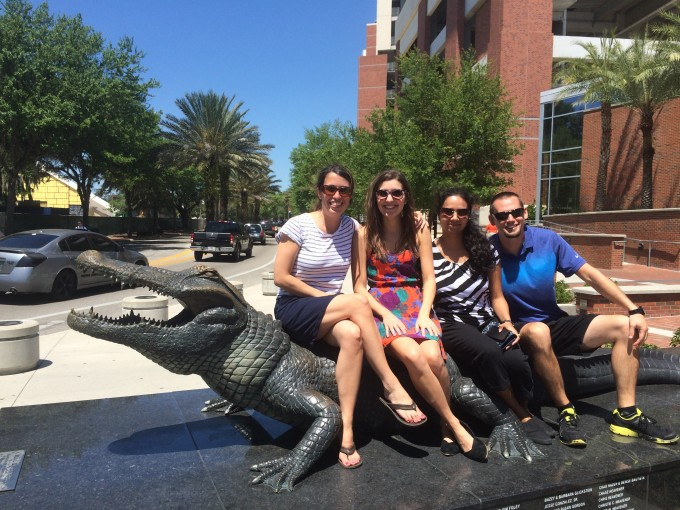 Four lab team members sitting on top of gator statue